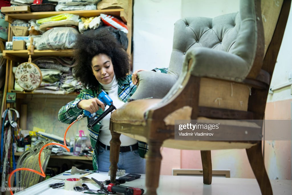African woman renovating a chair in upholstery workshop : Stock Photo