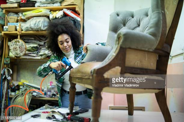 African woman renovating a chair in upholstery workshop