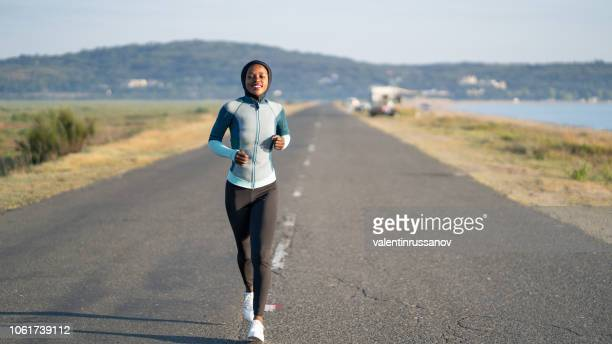african woman running with hijab - muslim woman beach stock photos and pictures