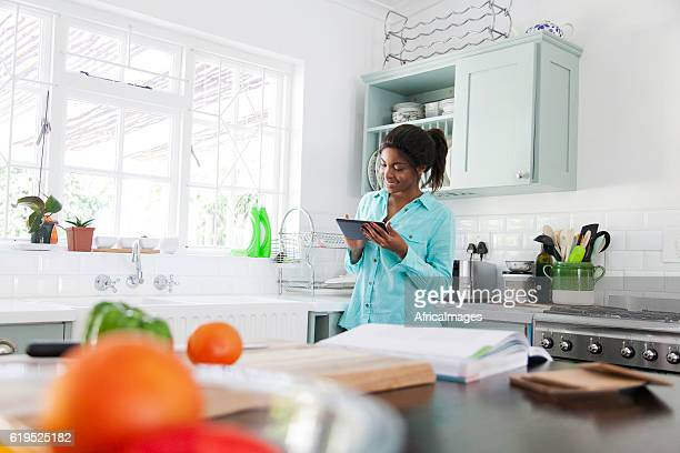 African woman searching the internet for a recipe.