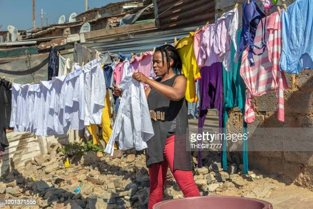 african woman seen hanging up her washing in alexandra township - gauteng province stock pictures, royalty-free photos & images