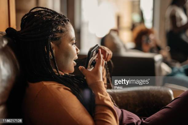 african woman sending voice message on mobile phone - speech recognition stock pictures, royalty-free photos & images