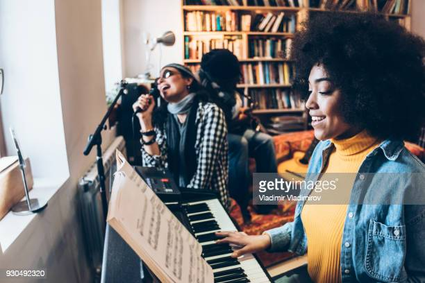 african woman singing and playing the piano with friends - musician stock pictures, royalty-free photos & images