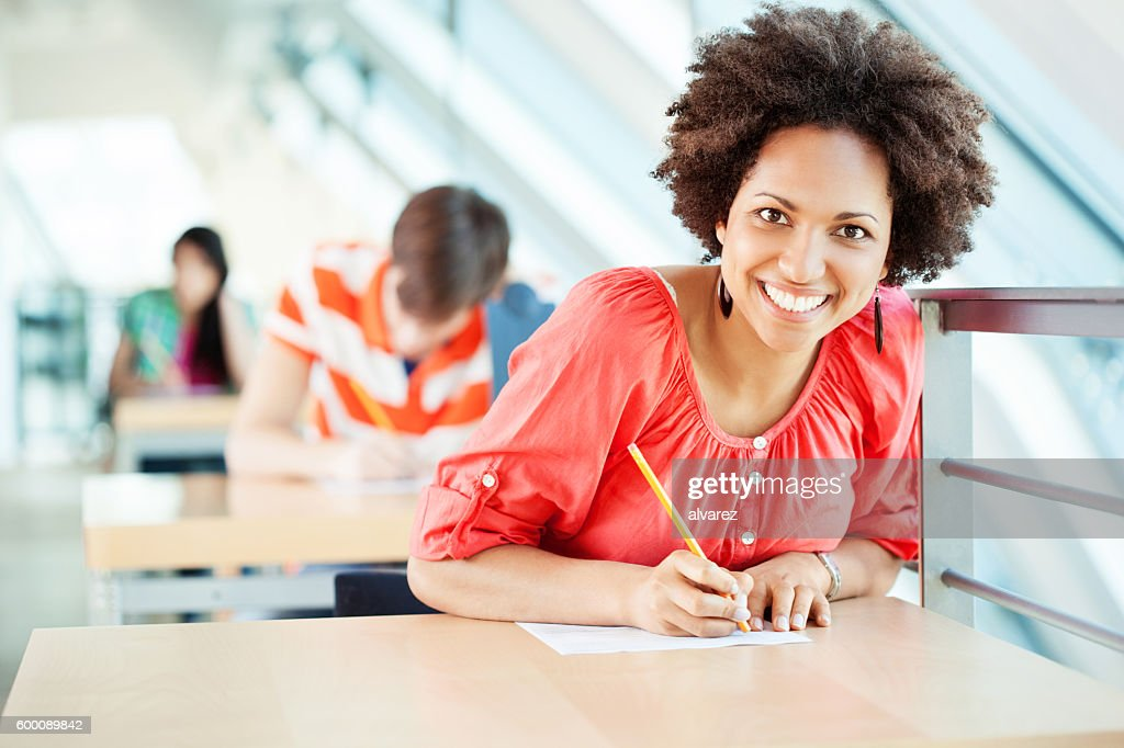 African woman sitting at an exam in college : Stock Photo