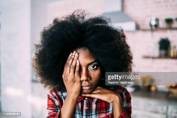 femme africaine s'asseyant à la maison, cachant le visage - violence photos et images de collection