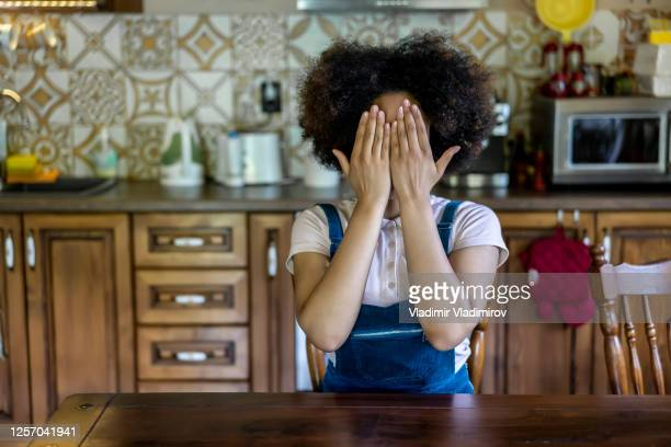 african woman sitting at home, hiding face - female torture stock pictures, royalty-free photos & images