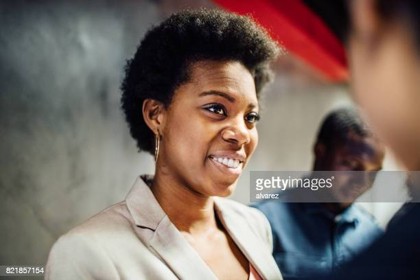African woman smiling during a discussing with colleague