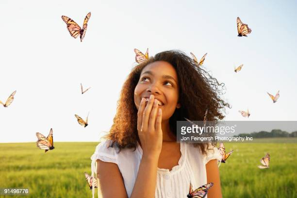 African woman standing among butterflies in meadow