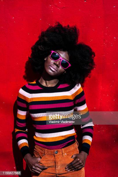African woman standing hands in pockets on red background