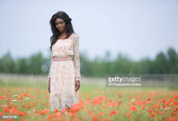 African woman standing in field of flowers