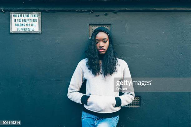 african woman standing near the wall with warning sign - street style stock pictures, royalty-free photos & images