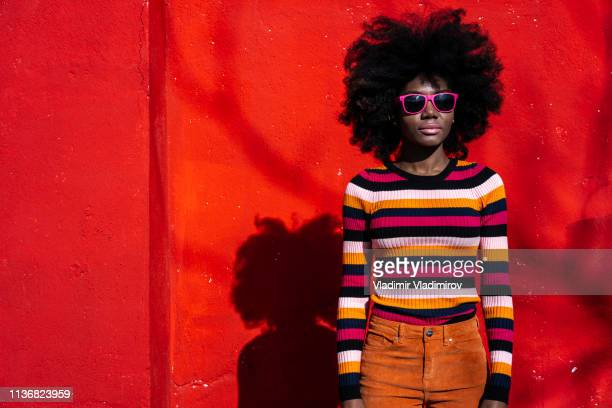 african woman standing on red background - afro stock pictures, royalty-free photos & images