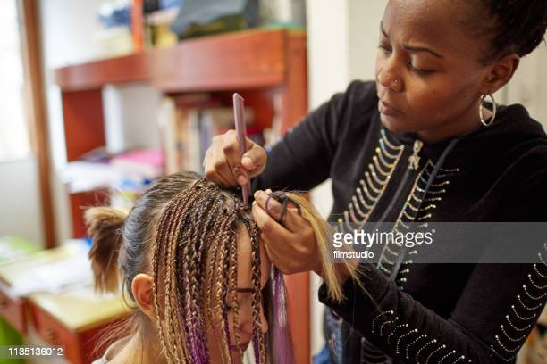 african woman styling friend's hair - braided stock pictures, royalty-free photos & images