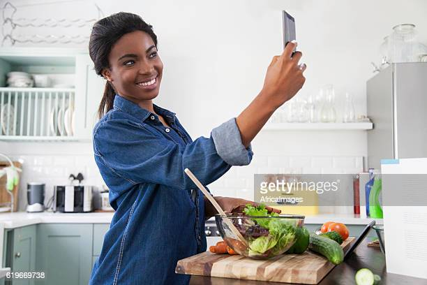 African woman taking a selfie in the kitchen.