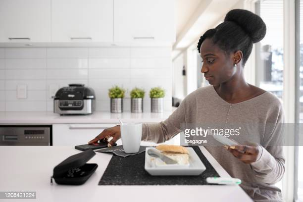 african woman taking blood sugar level in different time of the day - lancet arch stock pictures, royalty-free photos & images
