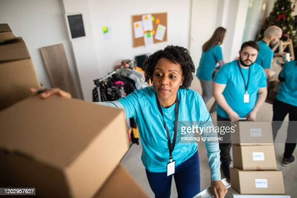 african woman taking donation box from shelf - charity and relief work stock pictures, royalty-free photos & images