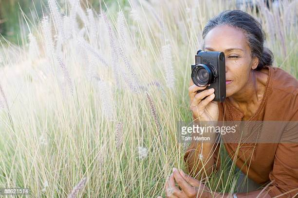 african woman taking photographs outdoors - hobbies stock pictures, royalty-free photos & images