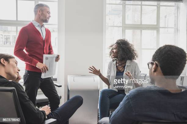 African woman talking to manager in red cardigan at business meeting with two other colleagues