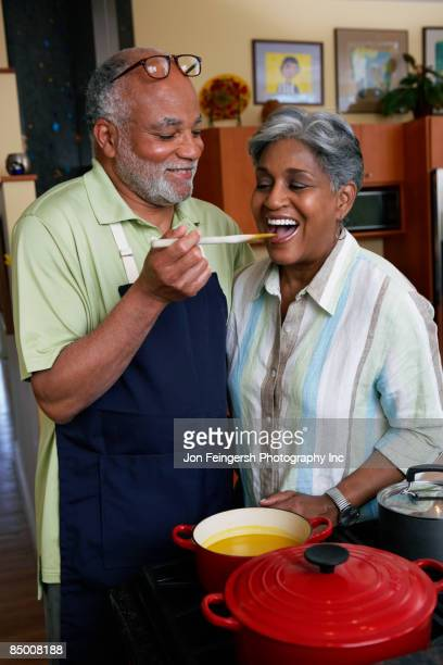 African woman tasting husband's cooking