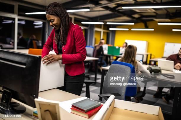 boîte de déballage de femme africaine au nouveau bureau - 1er jour d'un événement photos et images de collection