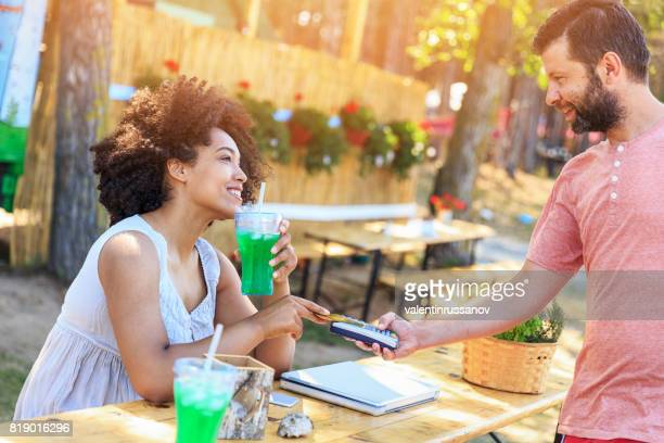 African woman using credit card outdoors
