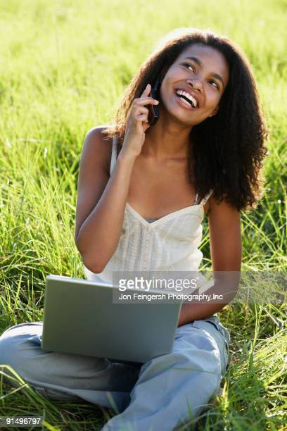African woman using laptop and cell phone in meadow