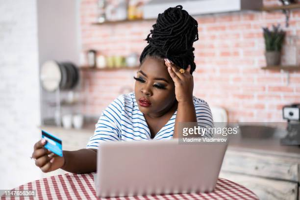 african woman using laptop and having problems with credit card - fee stock pictures, royalty-free photos & images