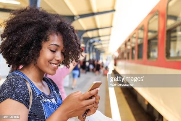 Afrikanerin mit Smartphone am Bahnhof