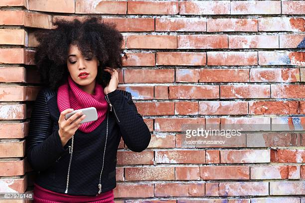 African woman using smart phone on street