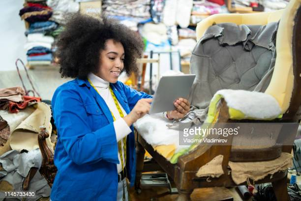 african woman using tablet in upholstery studio. - interior designer stock pictures, royalty-free photos & images