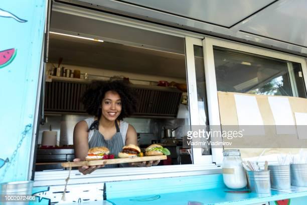 African woman vending burgers in food truck