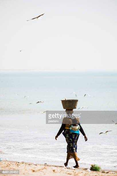 African woman walking at the beach - Gambia