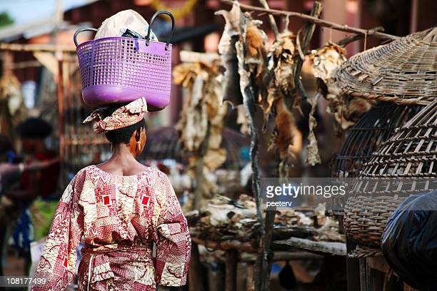 african mujer caminando a través de mercado - áfrica del oeste fotografías e imágenes de stock