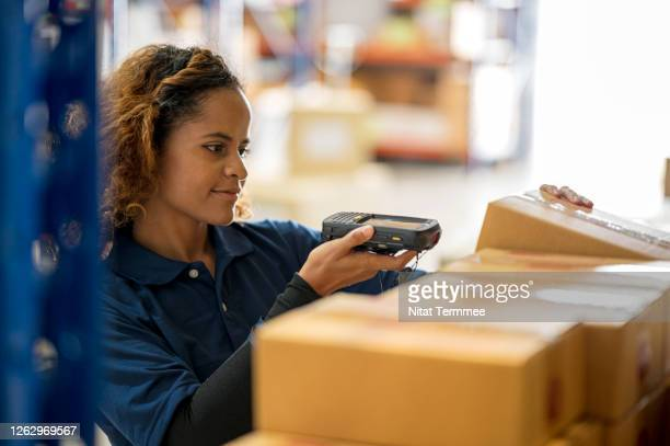 african woman warehouse worker scanning goods in cardboard box with bar code reader. taking inventory, warehouse management system. - polo shirt stock pictures, royalty-free photos & images