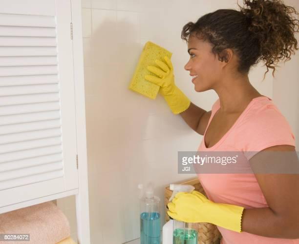 African woman washing wall