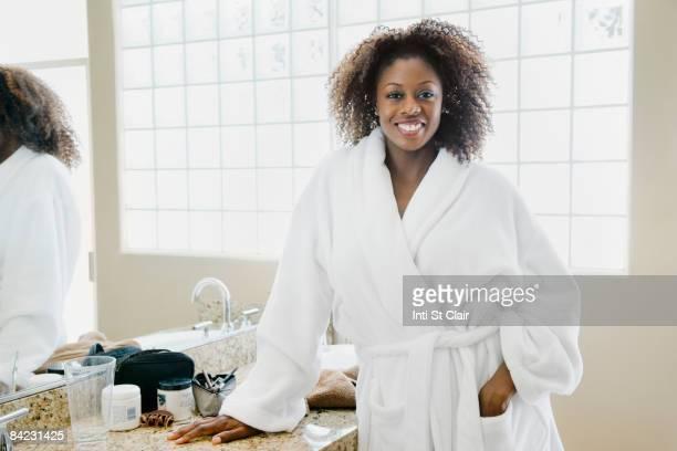 African woman wearing bathrobe in bathroom