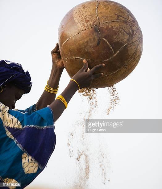 african woman winnowing grain - hugh sitton stock-fotos und bilder