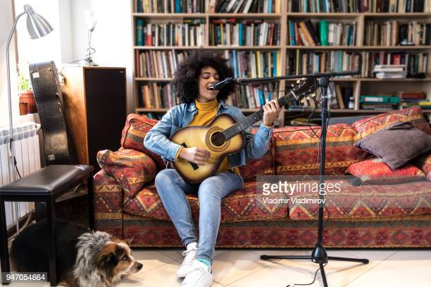 african woman with a dog playing guitar and singing - guitarist stock pictures, royalty-free photos & images