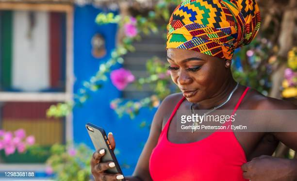 african woman with african headdress on the tropical part of ghana with cellphone in hand - multi colored dress stock pictures, royalty-free photos & images