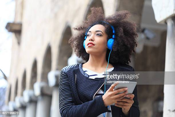 African woman with blue headphones listening music on digital tablet