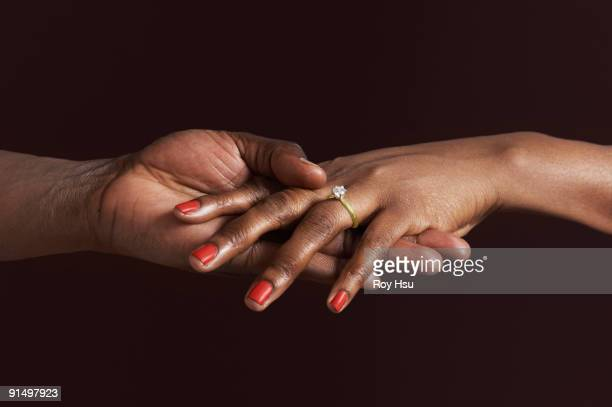 african woman with engagement ring holding fiancee's hand - fidanzato foto e immagini stock