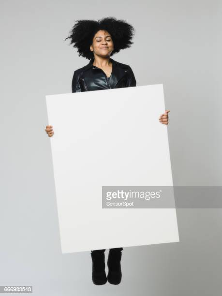African woman with eyes closed holding a blank billboard