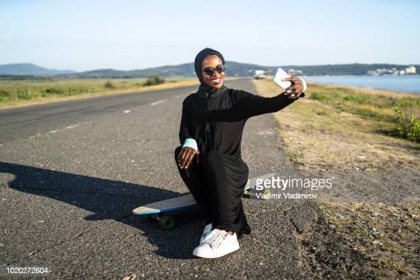 African woman with hijab taking selfie on skateboard
