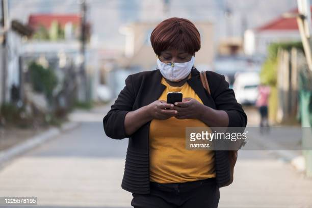 african woman with homemade facemask using mobile phone - obscured face stock pictures, royalty-free photos & images