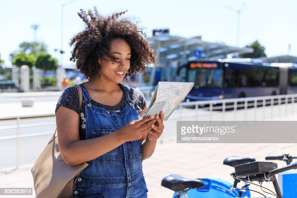 african woman with map taking a bike - bicycle parking station stock photos and pictures