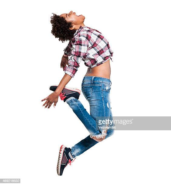 African woman with shirt tied above stomach in mid jump