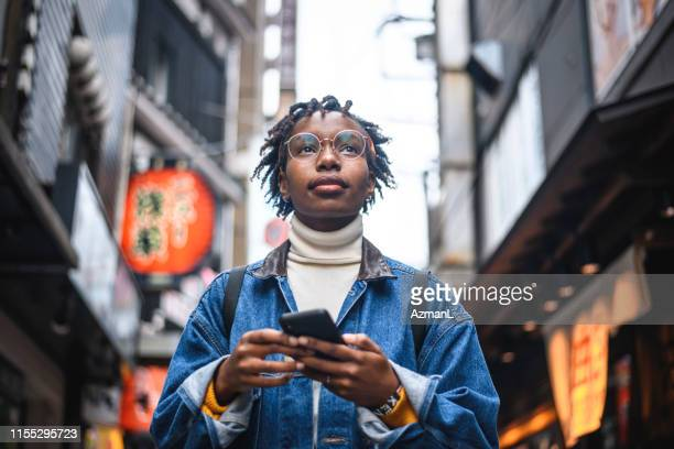african woman with smartphone vacationing in tokyo - cultures stock pictures, royalty-free photos & images