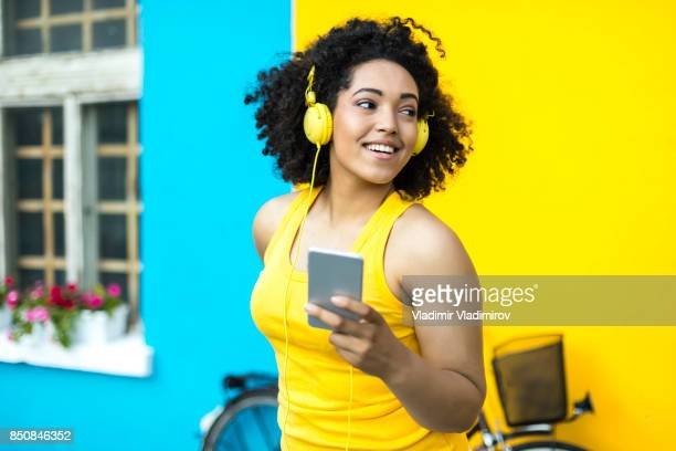african woman  with yellow headphones using smart phone - colore brillante foto e immagini stock