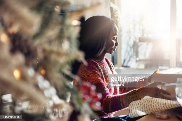 african woman wrapping gifts - donna bendata foto e immagini stock