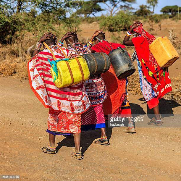 African women from Maasai tribe carrying water, Kenya, East Africa